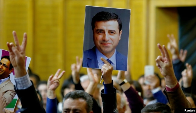 FILE - A supporter holds a portrait of Selahattin Demirtas, detained leader of Turkey's pro-Kurdish opposition Peoples' Democratic Party at a meeting at the Turkish parliament in Ankara, Nov. 8, 2016.