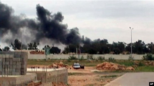 Plumes of smoke rising into the sky at Benina, a civilian and military airport, outside Benghazi in eastern Libya, Mar 17 2011