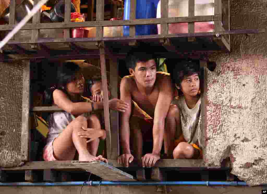 Cư dân quan sát người tình nguyện dọn dẹp lại khu vực bị ảnh hưởng nặng nề do lũ lụt ở ngoại ô thành phố Quezon, phía bắc thủ đô Manila, 12 tháng 8, 2012.