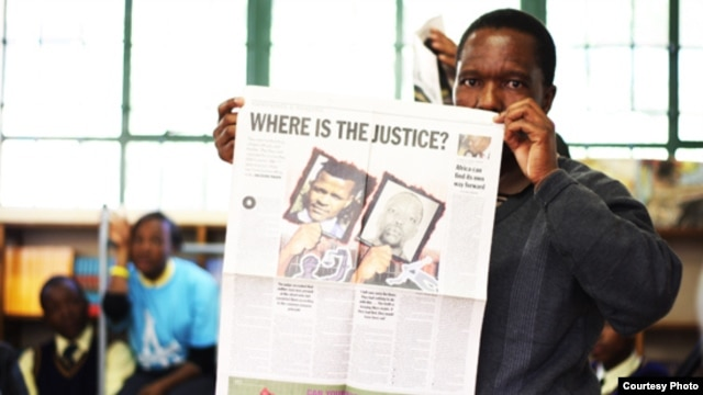 Tshokolo Mokoena, now 51, holds up a newspaper shortly after his release from prison after 19 years for a crime he says he did not commit. (Wits Justice Project)