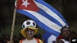 ພວກແຟນກິລາທີ່ເຊຍນັກເຕະບານຄີວບາ ລໍຖ້າເບິ່ງນັກກິລາ ທີ່ຈະລົງເດີ່ນເພື່ອແຂ່ງຂັນໃນຮອບຄັດເລືອກກິລາເຕະບານ ຫລື World Cup 2014 ຕໍ່ການາດາໃນກຸງຮາວານາຂອງຄີວບາ ໃນວັນສຸກທີ 8 ມີຖຸນາ, 2012. (AP Photo/Franklin Reyes)