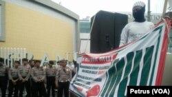 Polisi berjaga di depan Grand City Mall Surabaya, saat anggota FPI menyuarakan larangan pemakaian atribut non muslim bagi karyawan muslim , 18 Desember 2016 (Foto:VOA/Petrus Riski)