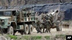 2013年4月18日在韓國首爾北部坡州的兩韓邊境之間﹐韓國士兵在軍事演習期間準備155毫米榴彈砲。