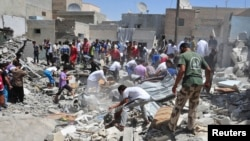 Men search for survivors amid debris of collapsed buildings after what activists said was an air raid by forces loyal to Syria's President Bashar al-Assad in Raqqa province, eastern Syria, August 10, 2013.