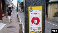 """东京路边灯柱上贴着带二维条码的广告,写着""""触一下,有便宜拿"""""""