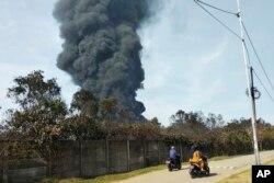 Pengendara motor melewati kepulan asap pekat akibat kebakaran kilang Balongan milik PT Pertamina, Indramayu,Jawa Barat, 29 Maret 2021. Ratusan orang dievakuasi dari desa terdekat setelah kebakaran besar terjadi di kilang tersebut. (Foto AP)