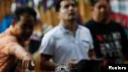 Nhân viên điều tra chỉ vào một vết đạn trên cửa sổ một quán cà phê sau vụ nổ súng gần khu du lịch Khao San Road ở Bangkok.