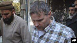 A U.S. consulate employee involved in a shootout that killed two Pakistani men is escorted by police after facing a judge in Lahore, January 28, 2011.