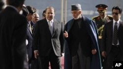 Afghan President Hamid Karzai, center right, talks with Pakistan's Prime Minister Nawaz Sharif while they inspect a guard of honor in Kabul, Afghanistan, in Nov 30, 2013.