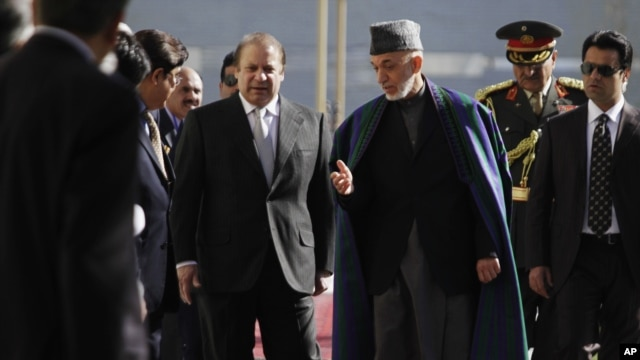 Afghan President Hamid Karzai, center right, talks with Pakistan Prime Minister Nawaz Sharif while they inspect honor guard, Kabul, Nov. 30, 2013.