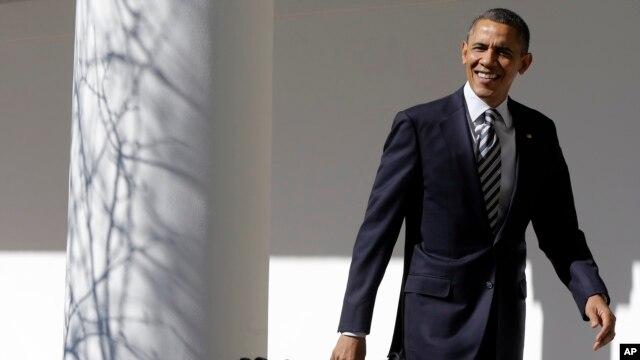 Presiden Obama tersenyum pada para wartawan yang meneriakkan pertanyaan-pertanyaan saat ia melalui West Wing Colonnade di Gedung Putih Selasa (12/2) sebelum menyampaikan pidato kenegaraan malam harinya.