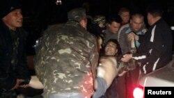 Warga membawa pria yang terluka dalam protes pro-Rusia dekat markas militer Ukraina di Mariupol (16/4).