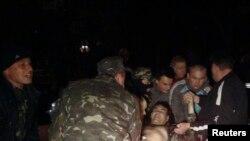 在4月16日烏克蘭東部軍事基地外受傷的武裝份子被抬離現場