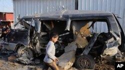 Seorang anak Irak berjalan melewati kendaraan yang hancur akibat serangan bom di kota Sadr dekat Baghdad, 8 Desember 2013 (Foto: dok).