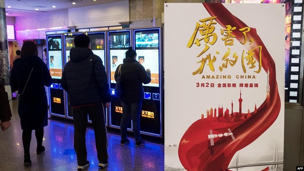 """2018年3月9日,上海一家电影院里的《厉害了我的国》影片海报。当局组织中国人去电影院观看这部颂扬共产党和习近平的宣传片 来自公司和政府机构工作人员的大量观看,使票房收入大增,国有媒体称其是该国有史以来收入最高的""""纪录片""""。"""