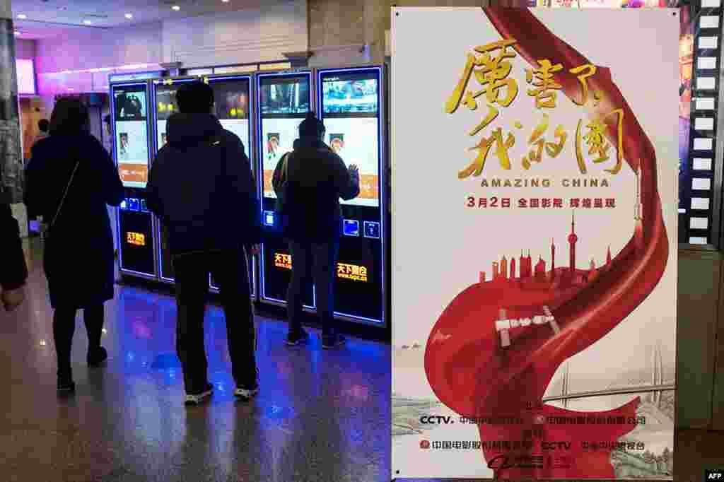 """2018年3月9日,上海一家电影院里的《厉害了我的国》影片海报。当局组织中国人去电影院观看这部颂扬共产党和习近平的宣传片。来自公司和政府机构工作人员的大量观看,使票房收入大增,国有媒体称这个电影是中国有史以来收入最高的""""纪录片""""。 但该片在美国主流电影信息网站IMDb上的用户评分曾经只有1分,是最低分。4月14日凌晨,评分为1.1分,有2600多人打分。最高分为10分。评分呈现两极分化,2400多人给1分,150人给10分。"""