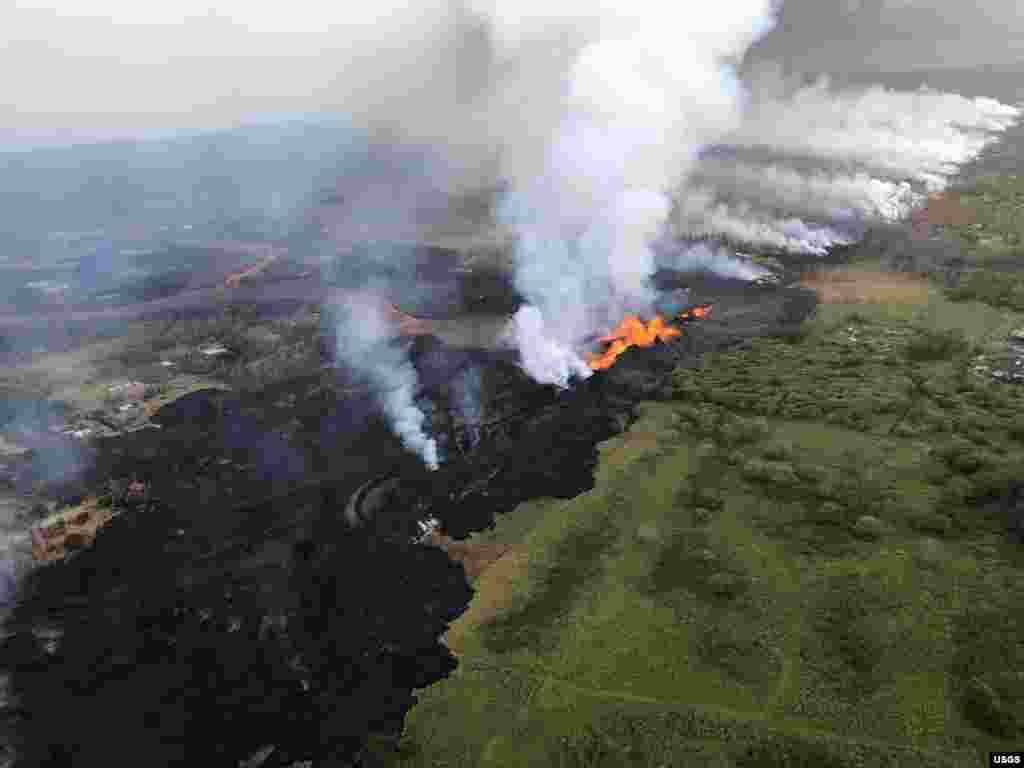 រូបភាពពីលើអាកាសបង្ហាញពីកម្អែលភ្នំភ្លើងហូរចេញទៅទិសខាងត្បូងអំឡុងការផ្ទុះភ្នំភ្លើងមួយកាលពីព្រឹកព្រលឹមនៃភ្នំ Kilauea ក្នុងរដ្ឋ Hawaii កាលពីថ្ងៃទី២១ ឧសភា ឆ្នាំ ២០១៨។