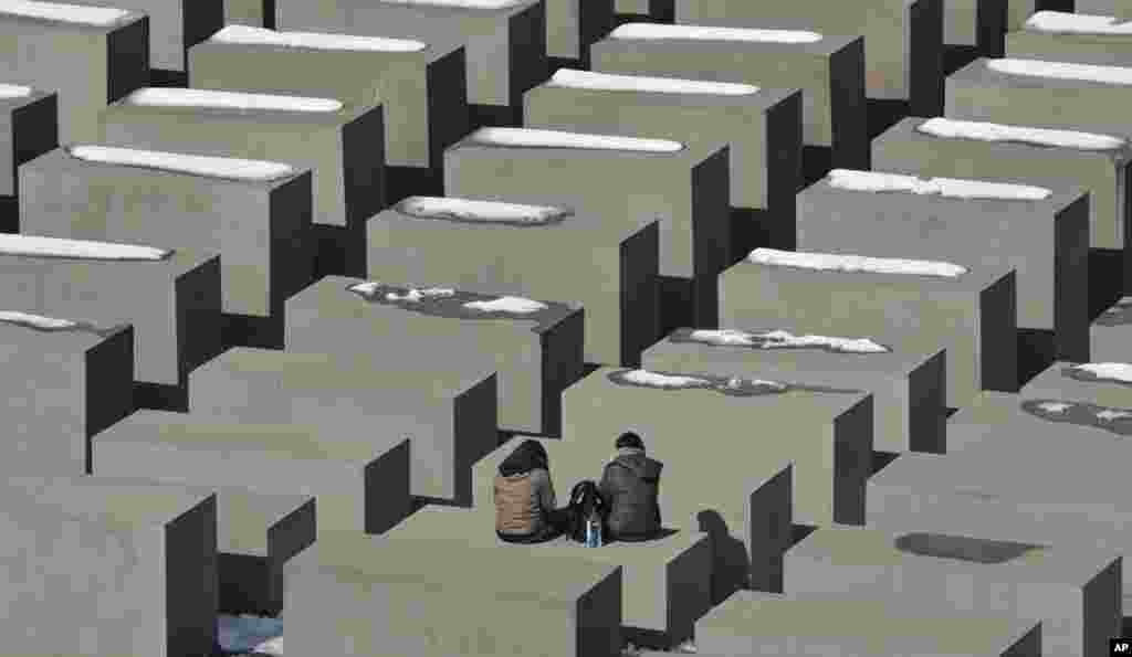 Tourists take a rest at the holocaust memorial in Berlin on a sunny, but cold, Monday.