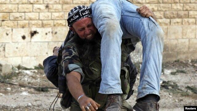 Ozod Suriya armiyasi jangchisi safdoshining jasadini olib ketmoqda