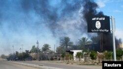 지난해 11월 이라크 바그다드 북부 사디야 지역에서 정부군과 이슬람 수니파 무장단체 ISIL의 무력충돌이 있은 후 ISIL 깃발 너머로 연기가 치솟고 있다. (자료사진)
