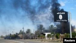 ຄວັນດຳທີ່ລອຍຂຶ້ນສູ່ທ້ອງຟ້າ ຢູ້ທາງດ້ານຫຼັງ ຂອງທຸງກຸ່ມລັດອິສລາມ ຫຼັງຈາກທີ່ ກອງກຳລັງຮັກສາຄວາມປອດໄພ ອີຣັກ ແລະ ພວກນັກຕໍ່ສູ້ ຊາວ Shiite ໄດ້ເຂົ້າຍຶດເອົາເມືອງ Saadiya ໃນແຂວງ Diyala ຈາກພວກຫົວຮຸນແຮງລັດອິສລາມ ເມື່ອວັນທີ 24 ພະຈິກ 2014.