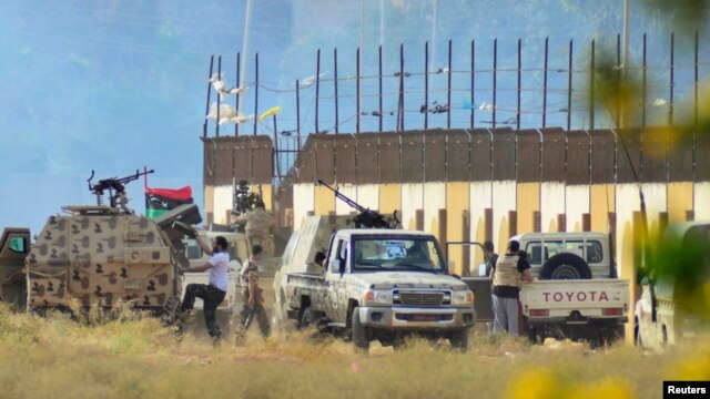 Irregular forces loyal to former army general Khalifa Haftar stand with armed vehicles during clashes with Islamist militants, Benghazi June 2, 2014.