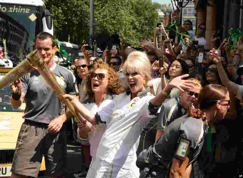 In this photo provided by LOCOG, British actresses Joanna Lumley, center right, and Jennifer Saunders, center left, carry the Olympic Flame between Lambeth and Kensington and Chelsea, in London, July 26, 2012.