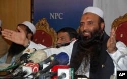 FILE - Saifullah Khalid, right, a longtime official of the banned militant Jamaat-ud-Dawa group, and president of the newly-formed Milli Muslim League party, addresses a news conference in Islamabad, Aug. 7, 2017.