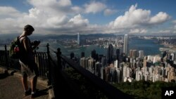 A tourist takes a picture from the Victoria Peak in Hong Kong.