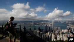 A tourist takes a picture from the Victoria Peak in Hong Kong