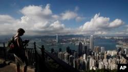 一名遊客在山頂俯瞰香港維多利亞灣。