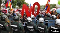 Police officers block a street as protesters march to the Cambodia National Assembly during a protest in Phnom Penh July 13, 2015. Cambodia passed on Monday a contentious law to regulate non-governmental organisations (NGOs) which government critics fear will be used to muzzle opposition. REUTERS/Samrang Pring