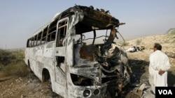 Seorang pria mengamati kerusakan bus yang terbakar akibat bertabrakan dengan mobil tangki minyak di Pakistan.