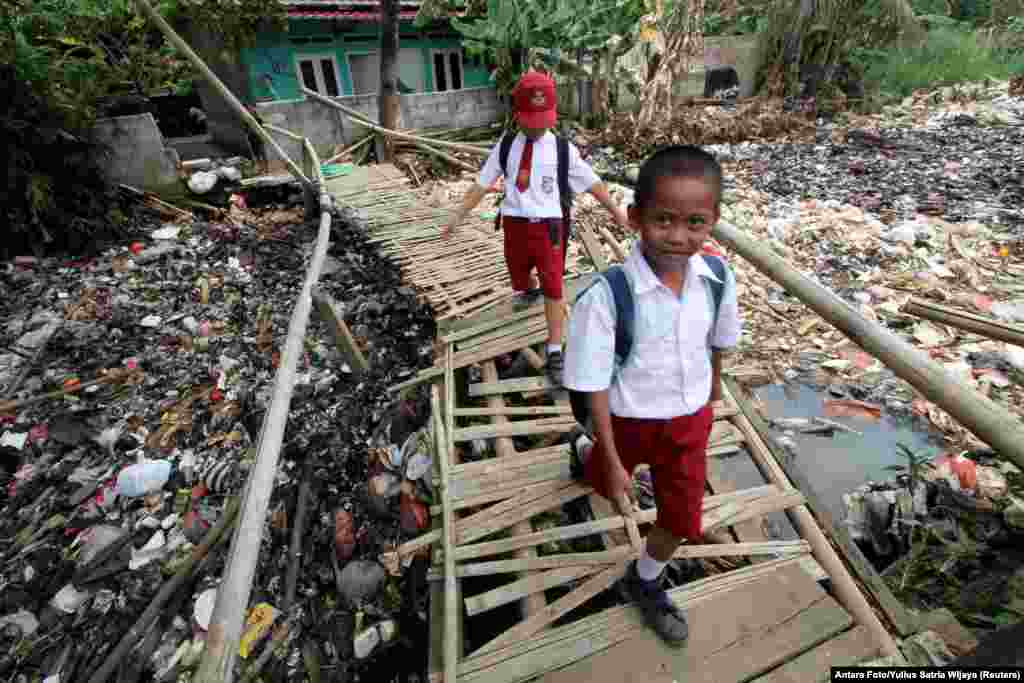 Students cross a bamboo bridge, above a garbage-filled stream branching off the Ciliwung River, in Bogor, Indonesia.