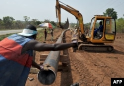 FILE - Workers of Ivory Coast Kuyo pipeline company assemble pipelines in Tiebissou, near Abidjan, the economical capital of Ivory Coast.