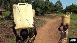 Trẻ em đội nước đi trên những con đường đất đỏ ở Lira