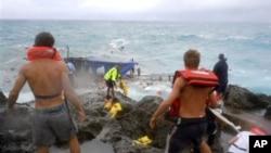 Regu penyelamat berupaya menolong para pencari suaka yang kapalnya terbalik di lepas pantai pulau Crismas, Samudra Hindia (Foto: dok). 93 orang dilaporkan berhasil diselamatkan, dua orang tenggelam dan dua orang cedera serius saat kapal meeker ditemukan terbalik di wilayah tersebut, Senin (25/3).
