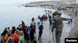 A Spanish legionnaire indicates the direction to follow to Moroccan citizens on El Tarajal beach, as they get out of the water on the Spanish side of the fence between the Spanish-Moroccan border, after thousands of Moroccans swam across this border on Mo