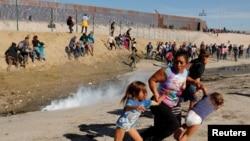 Maria Lila Meza Castro (giữa), một người mẹ di dân 39 tuổi từ Honduras, chạy tránh hơi cay cùng voo71i hai con gái Saira Nalleli Mejia Meza (trái) và Cheili Nalleli Mejia Meza (phải) trước bức tường biên giới giữa Mỹ và Mexico, ở Tijuana, Mexico, ngày 25 tháng 11, 2018.