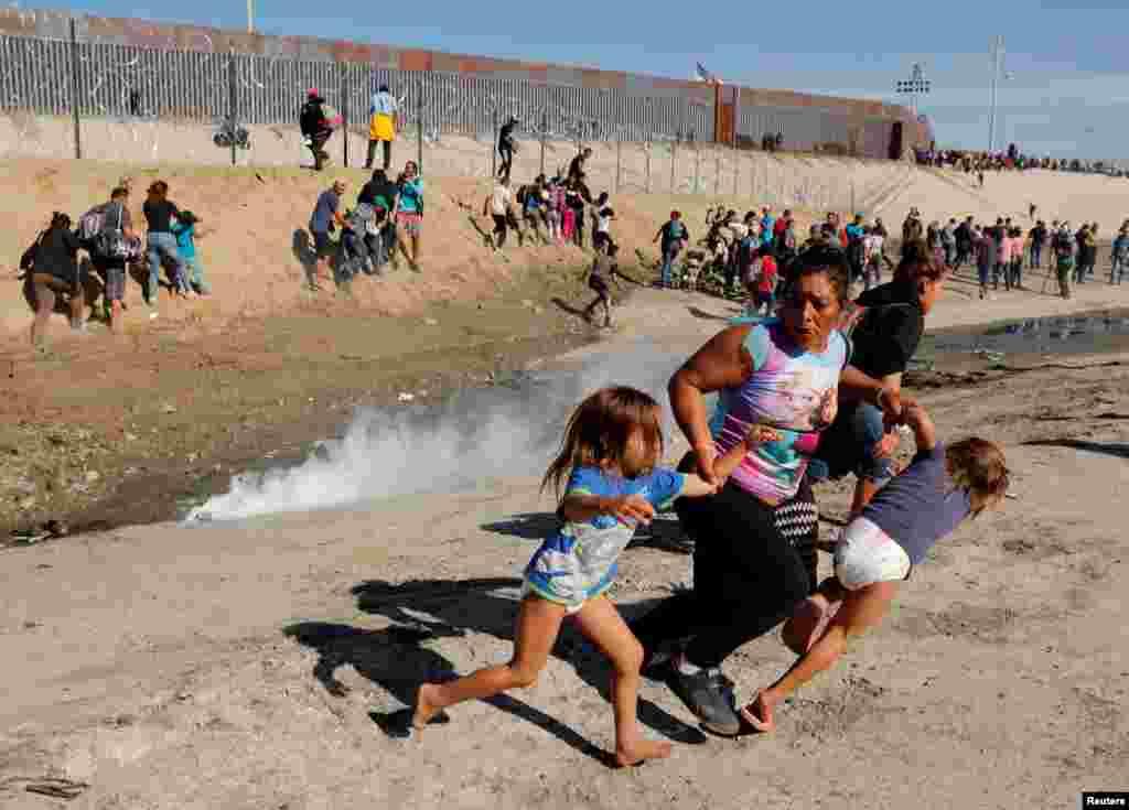 امریکہ اور میکسیکو کے درمیان سرحد پر کارواں میں شامل ہنڈورس سے تعلق رکھنے والی 39 سالہ تارکِ وطن خاتون اپنی 5 سالہ جڑواں بیٹیوں کے ساتھ آنسو گیس سے بچنے کےلیے بھاگ رہی ہے۔