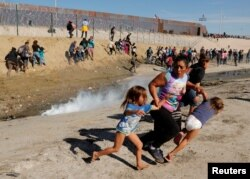 Maria Lila Meza Castro (C), a 39-year-old migrant woman from Honduras, runs away from tear gas with her five-year-old twin daughters Saira Nalleli Mejia Meza (L) and Cheili Nalleli Mejia Meza (R) in front of the border wall between the U.S and Mexico, in Tijuana, Nov. 25, 2018.