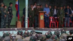 President Rodrigo Duterte (center, at podium) clenches his fist as he declares the liberation of Marawi after an almost five-months long battle to oust Islamic State fighters from the city, in Marawi, Philippines, Oct. 17, 2017.