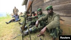 M23 rebel fighters rest at their defense position in Karambi, eastern Democratic Republic of Congo (DRC) in north Kivu province, near the border with Uganda, July 12, 2012.