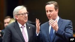 Presiden Komisi Uni Eropa Jean-Claude Juncker (kiri) berbicara dengan PM Inggris David Cameron pada KTT pemimpin Uni Eropa di Brussels, Belgia (18/2).