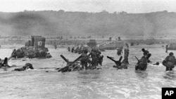Some of the first assault troops to hit the beach of Normandy, France, on June 6, 1944 take cover behind enemy obstacles to fire on German forces as others follow the first tanks through the water toward the German-held shore during World War II