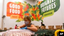 Volunteers pack boxes of food for distribution, at The Capital Area Food Bank, in Washington, Oct. 5, 2021.