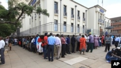 FILE: In this photo taken on Tuesday, May, 3, 2016, Zimbabweans wait in a long line to withdraw cash in Harare. Severe shortages of U.S dollars that are used as local currency have forced many residents into cash hunter-gatherers.