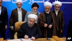 "In this photo released by the office of the Iranian Presidency, President Hassan Rouhani signs the ""Charter of Citizenship Rights"" in Tehran, Dec. 19, 2016."