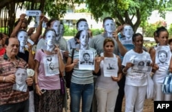 FILE - Cuban dissidents pose wearing masks depicting US President Barack Obama and holding pictures of imprisoned dissidents as they protest against the reopening of the US embassy in the island, Aug. 9, 2015.