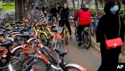 Residents ride bicycles from bike-sharing companies in Beijing, China. March 23, 2017. (AP Photo/Andy Wong)